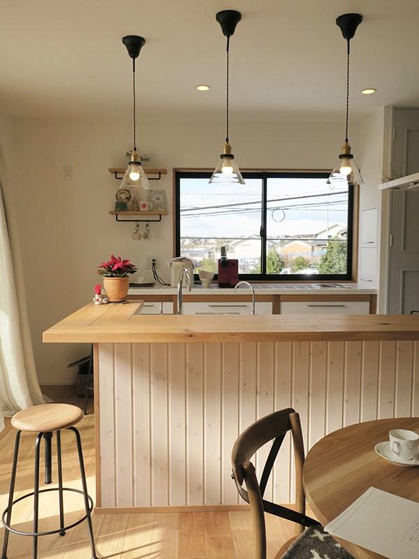対面キッチンのカウンターは、パイン材を使用してナチュラルな雰囲気に。