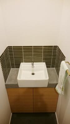 トイレを出たところにある手洗い。シンプルなスクエア型のシンクとオーダーの洗面台。タイルで汚れ防止。