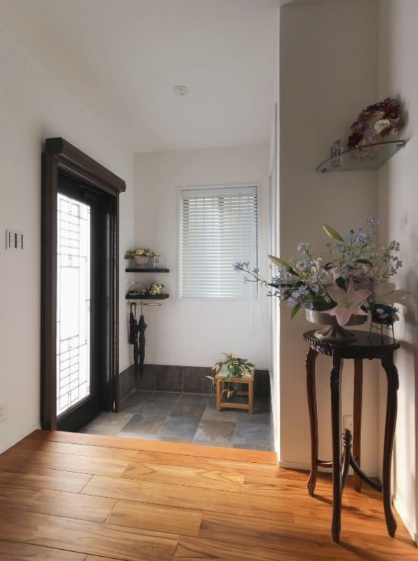 自然な色合いの石材タイルと床材の質感がマッチした玄関