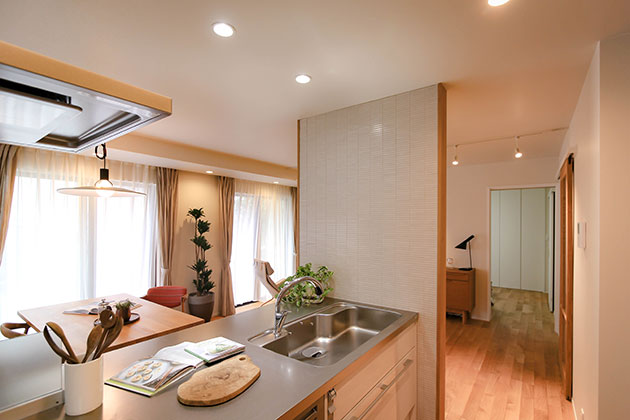 白いシステムキッチンに白タイルの壁